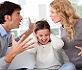 Parents arguing with child sat between them