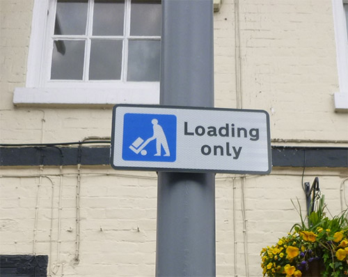 Close up of a loading sign denoted by a man with a wheeled trolley
