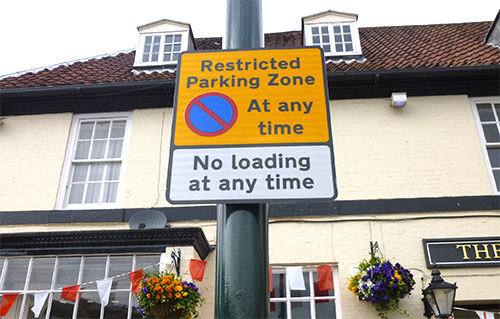 A close up of a repeater sign - 'Restricted Parking Zone. No Parking at any time. No loading at any time.'